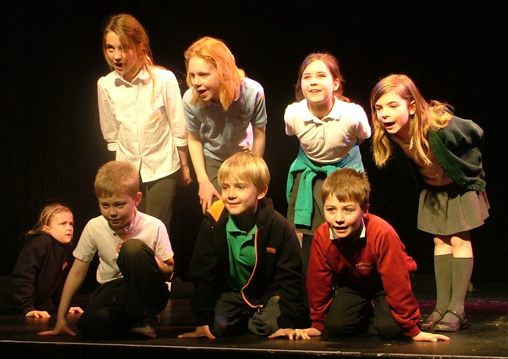 Children standing on a stage, acting in a play